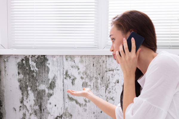 mulher pedindo ajuda perto da parede