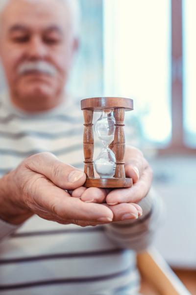 idoso segurando ampulheta em asilo simbolo