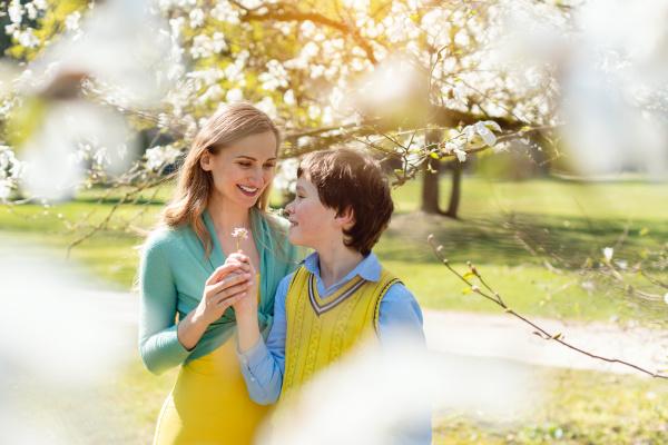 filho dando flores para a mae
