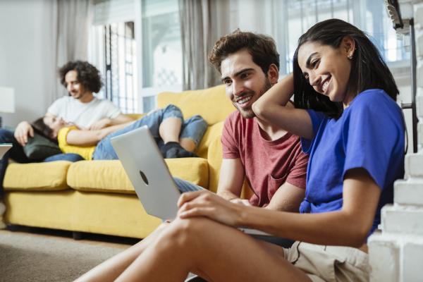 casal jovem sorridente compartilhando laptop enquanto