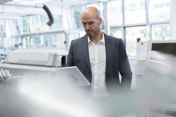 empresario careca olhando para tablet digital