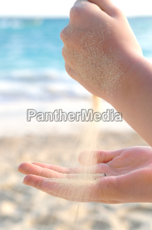 hands pouring sand on a beach