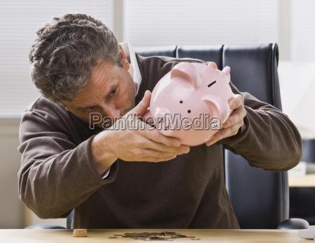 homem que olha o banco piggy