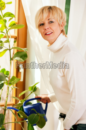 woman pours her houseplants