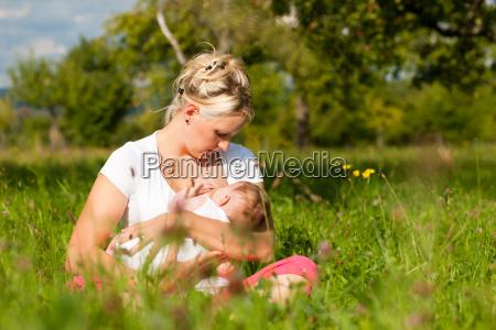 mae amamentando o bebe no prado