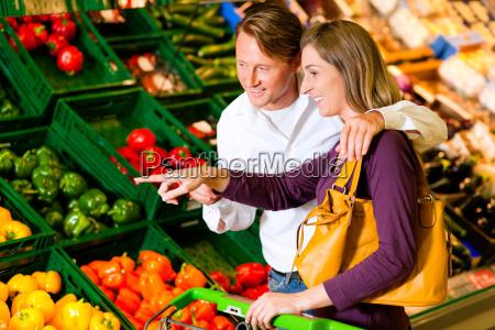 casal no supermercado compra legumes