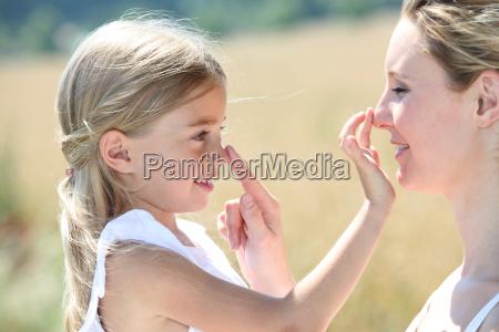 mae e filha colocando protecao solar