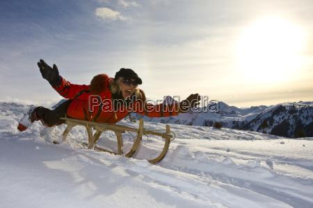 kobieta jedzie sankach w sniezny krajobraz