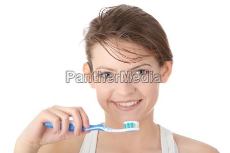 rapariga que escova seus dentes feliz