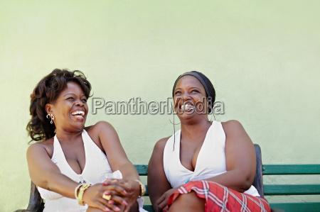 mulheres negras com vestido branco rindo