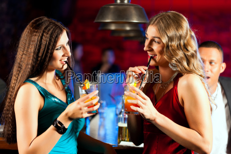 people with cocktails in bar or