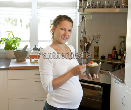 mulher nova gravida com salada