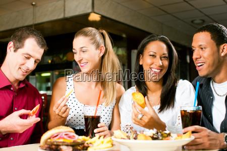 friends eating hamburger and drinking cola