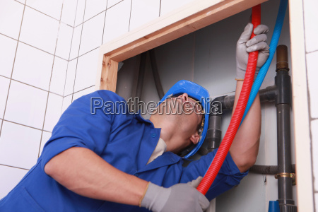 plumber feeding flexible pipes behind a