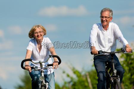 casal feliz que monta uma bicicleta
