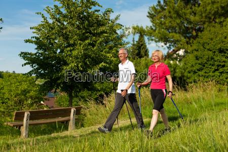 casal de idosos caminhada nordica feliz