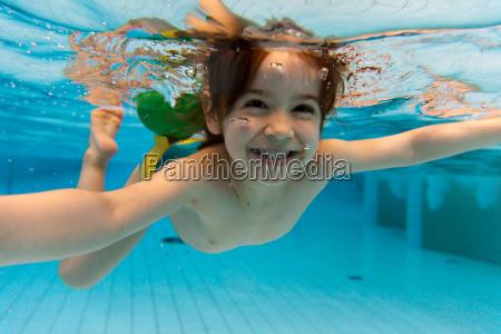 a menina sorri nadando a agua