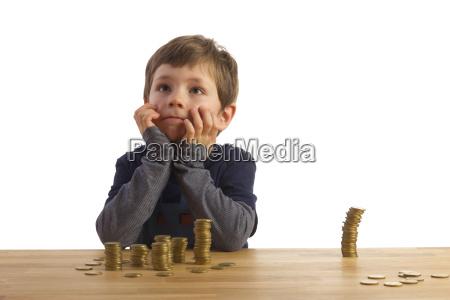 um menino sentando frente varios pilhas