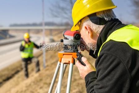 geodesist measure land with tacheometer highway