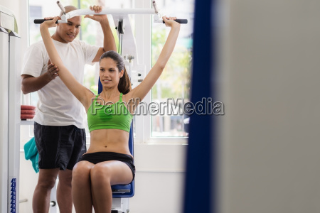 personal trainer helping woman training in