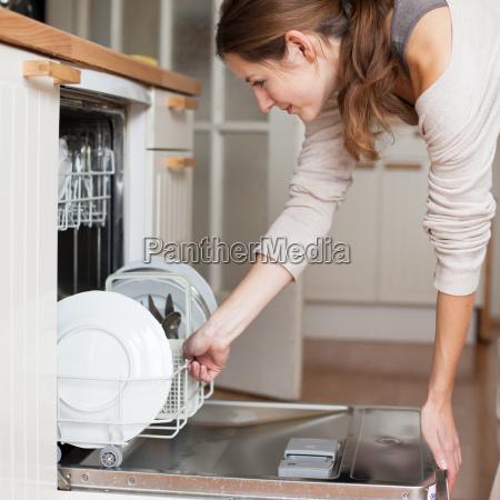 trabalho domestico jovem colocando pratos na