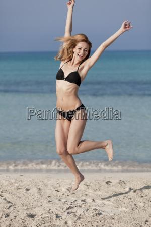 woman with bikini jumps happily on