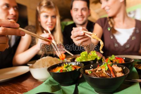 os jovens comendo em um restaurante