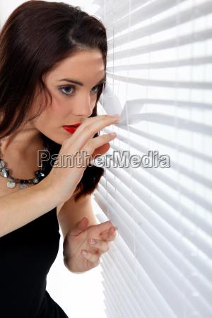 mulher que perscrutam atraves das cortinas