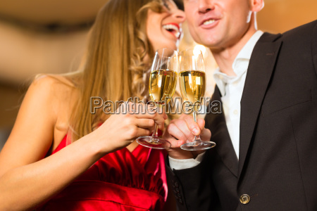 man and woman drinking champagne in