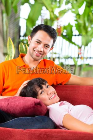 pares asiaticos em casa no sofa