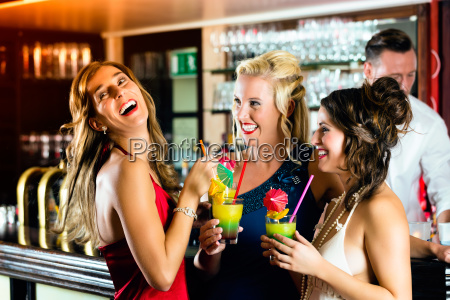 women with cocktails in a bar