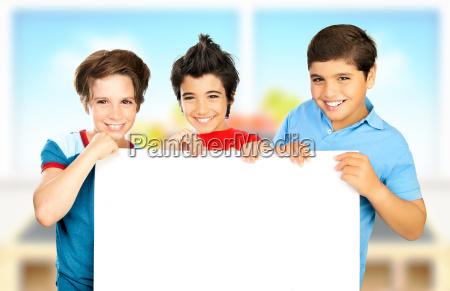 three boys in classroom holding white