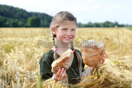 menina com pao no campo de