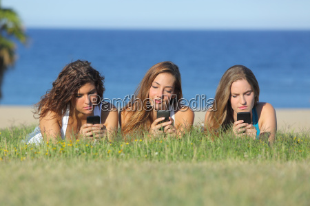 group of three teenager girls typing