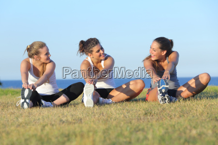 group of three women stretching after