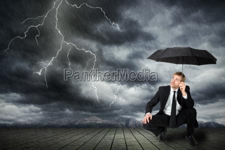 homem de terno e guarda chuva
