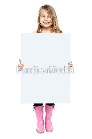 um garoto adoravel mostrando quadro branco