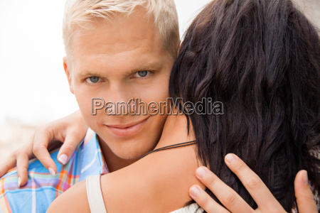 blond young man hugging his girlfriend