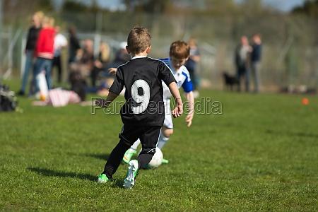 dois meninos jogando futebol
