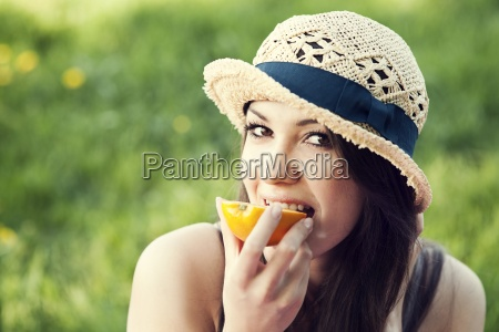 beautiful woman eating orange on meadow