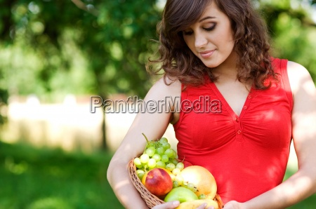 young woman holding basket filled mix
