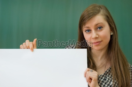 young woman in classroom holding white
