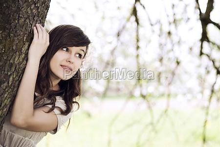 beautiful young woman hiding behind tree