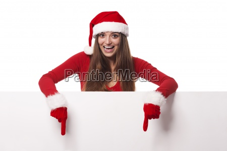 excited woman wearing santa hat showing