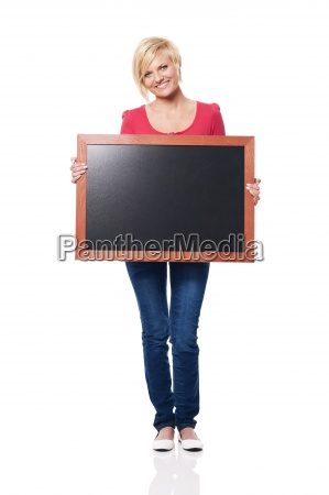 smiling woman holding blackboard