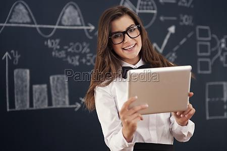 smiling teacher using digital tablet