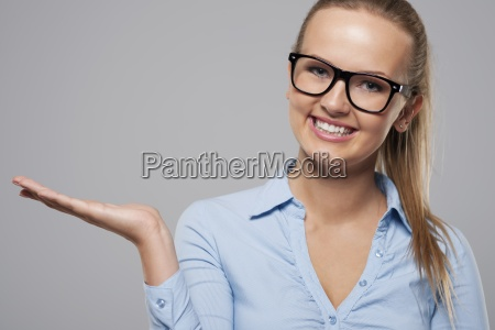 smiling woman wearing fashion glasses presenting