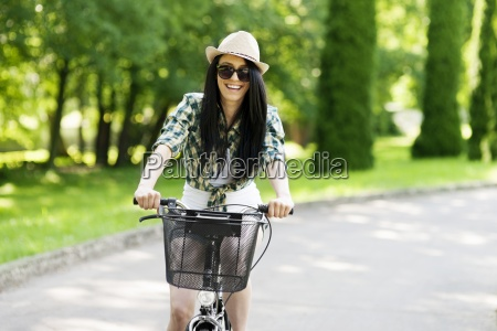 happy young woman cycling through the
