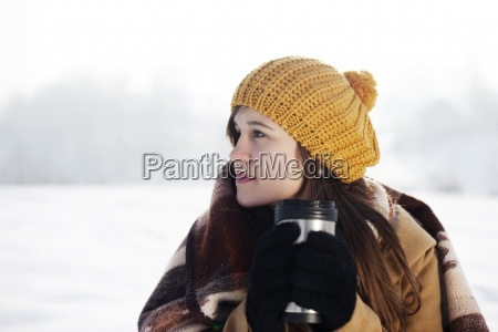 young woman drinking hot drink outdoors