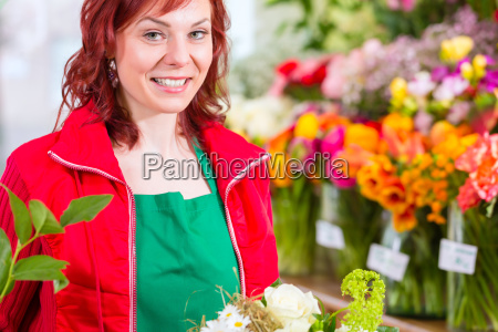 florist binds bouquet in the store